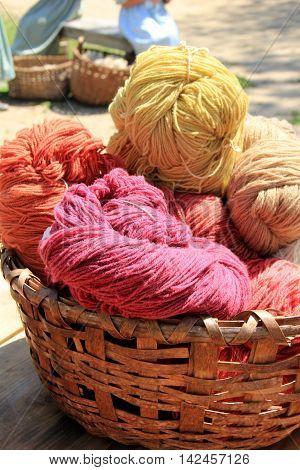 Wicker basket holding colorful; skeins of wool yarn
