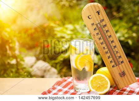 thermometer shows a high temperature during heat wave. Lemon drink.