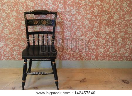 Simple image of old, weathered chair on warm wood planked flooring, set against colorful wall in rural country home.