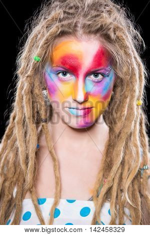 Portrait of young blond woman with colorful face and dreadlocks. Isolated on black