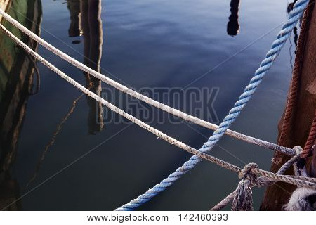 Nautical background. Closeup of an old blue frayed boat rope. Tonned image.