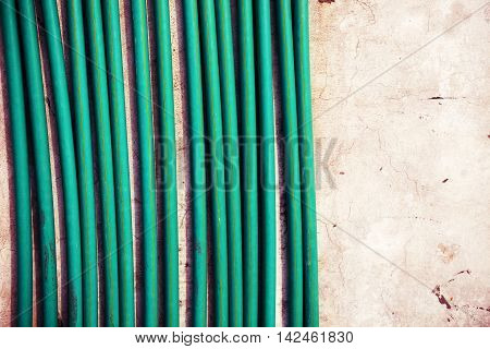 wall in residential house building construction site with green cable wires shrouded hard pipe tube plastic