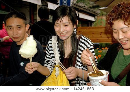 Chengdu. China - September 19 2006: A Chinese family enjoying a variety of food snacks including cotton candy on historic Jin Li Street