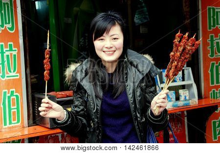 Chengdu China - January 21 2008: Smiling young Chinese woman holding spicy barbecued meat on wooden sticks at a food stall on Chunjie Road