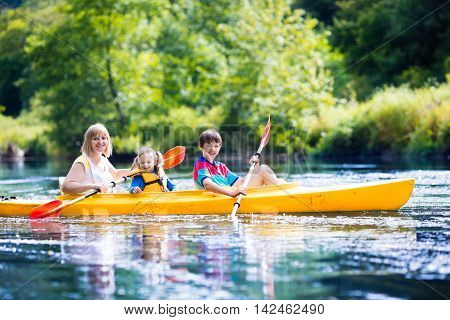 Happy family with two kids enjoying kayak ride on beautiful river. Mother with little girl and teenager boy kayaking on hot summer day. Water sport fun. Canoe and boat for children.