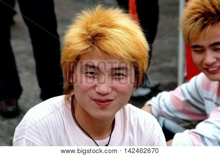 Yangshuo China - April 29 2008: Chinese youth with dyed blond hair hanging out with friends on West Street