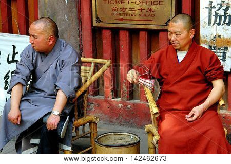 Chengdu China - April 25 2005: Two Buddhist monks sitting in bamboo chairs in front of the Wenshu Temple at the Manjursi Monastery