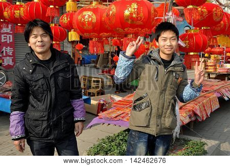Jun Le China - January 25 2014: Friendly teenage Chinese youth with his father selling Chinese New Year decorations at a roadside booth