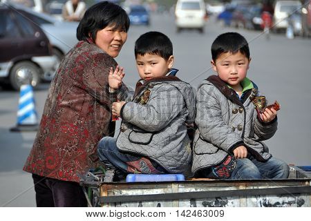 Pengzhou China - March 15 2010: Grandmother pushes a bicycle cart holding her twin grandsons after picking them up from school
