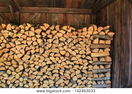 Wood shed with cords of freshly cut wood stacked neatly.