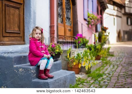Cute little girl in pink coat walking down a street in historical medieval city center on cold autumn day. Child during fall vacation in Eguisheim Alsace France. Travelling and tourism with kids.