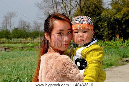 Pengzhou China - March 14 2014: Young Chinese mother with freckled face holding her baby son at a Sichuan province farm