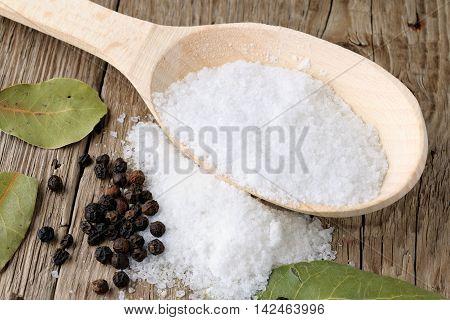 Salt in wooden spoon and black pepper