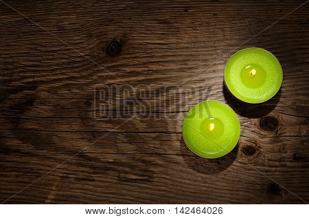 Two small candles old on wooden background