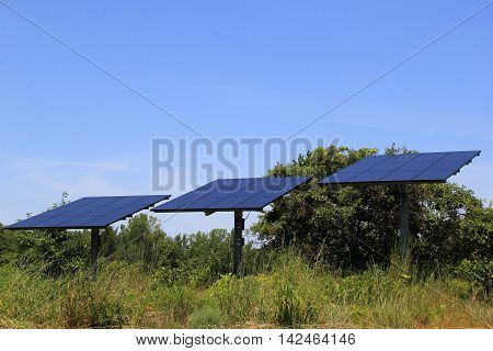 Three solar panels set out in the middle of a field