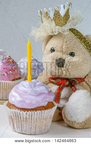 Cupcakes with a candle on the first birthday of a little girl. Against the background of a teddy bear with a hairclip in the form of a crown.
