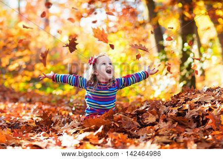 Happy little girl playing in beautiful autumn park on warm sunny fall day. Kids play with golden maple leaves.