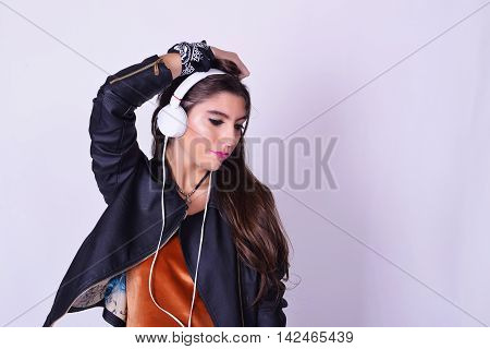 Young Hispanic Woman Listening To Music With Headphones