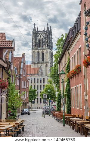 MUNSTER, GERMANY - AUGUST 7, 2016: Liebfrauenkirsche church and cobblestoned street in Munster, Germany