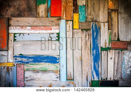 Photo of a well worn wooden wall with multicoloured planks and vignetting added.