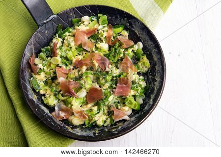 scrambled eggs with green onions and prosciutto in a black iron pan on green cloth and a white painted wooden background with copy space view from above
