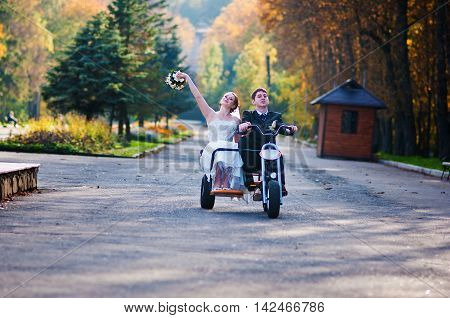 Happy Wedding Couple On Three Wheel Bike