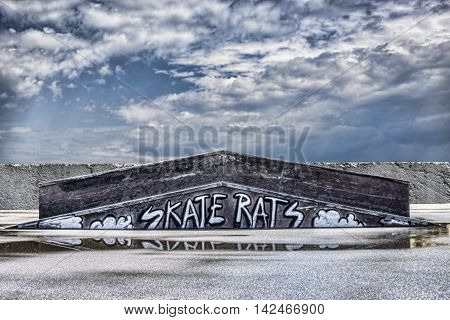 Abstract graffiti in skatepark concrete wall on sky background