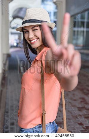 Joyful girl is showing peace sign and winking. She is standing in city and smiling
