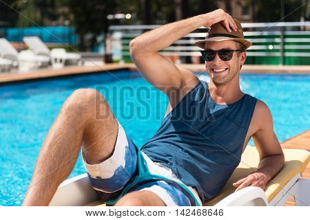 Brighten your life. Delighted smiling handsome man resting near swimming pool and smiling while lying on the sun bed