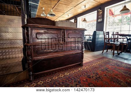 Old vintage wooden chest of drawers in pub interior