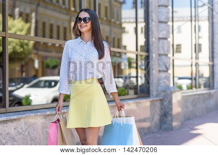 Happy young woman is going shopping. She is walking on street with packets and smiling