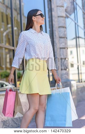Joyful female shopaholic is going to boutique. Girl is carrying colored packets and smiling