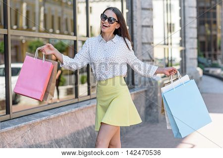 Carefree girl is walking from shop with packets. She is posing and smiling happily