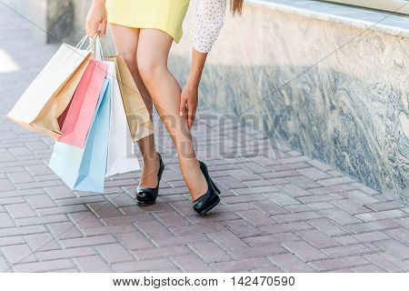 My legs are tired from shopping. Close up of young woman touching her foot. She is standing and holding packets