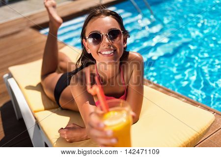 Here you are. Charming joyful smiling woman drinking cocktail and resting on the sun bed while spending time near swimming pool