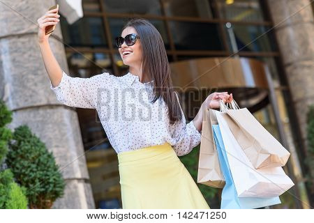 Joyful young woman is making selfie and smiling. She is carrying shopping packets. Lady is standing outdoors and holding smartphone