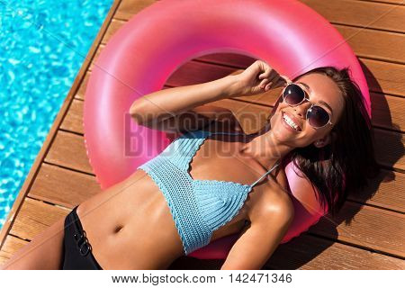 Have a good mood. Cheerful charming content woman lying on the inflatable ring and resting near swimming pool