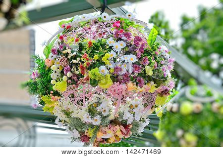 Beautiful floral outdoor street installation suspended in air. Planters made artificial flowers. Selective focus.