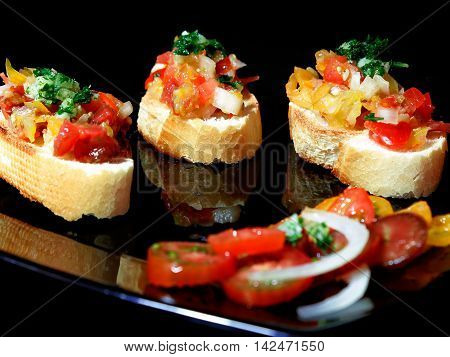 Bruschetta with different varieties of tomatoes parsley and garlic