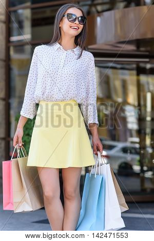 Fashionable young woman is standing near shop and smiling. She is holding packets and looking forward with happiness