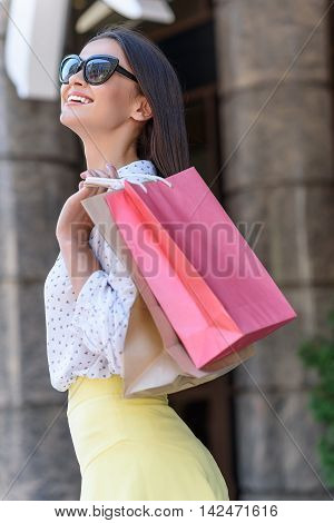 Carefree girl is posing with shopping packets. She is standing and laughing