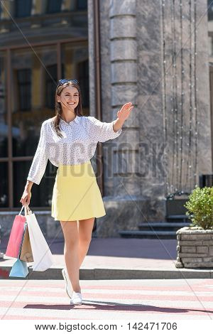 Taxi. Elegant young woman stops car. She is walking with shopping packets. Girl is raising arm and smiling