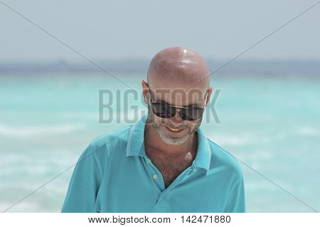 hairless middle-aged man on the beach in turquoise shirt