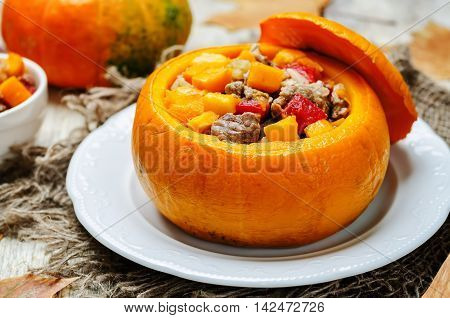 Pumpkin stuffed with meat and vegetables on wooden background