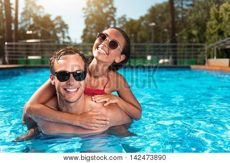 Happy together. Delighted overjoyed couple smiling and embracing while swimming in a pool