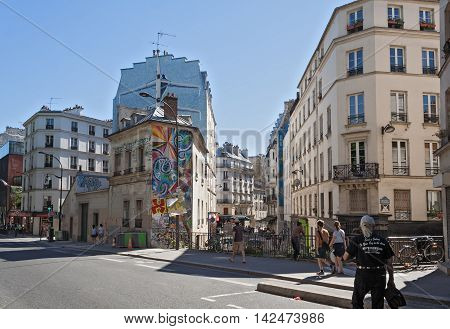 PARIS, FRANCE - AUGUST 9, 2016: tourists on the Quai de Valmy in the 10th arrondissement in Paris