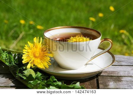 Dandelion tea in a white cup on a wooden table against a blurry dandelion meadow selected focus narrow depth of field