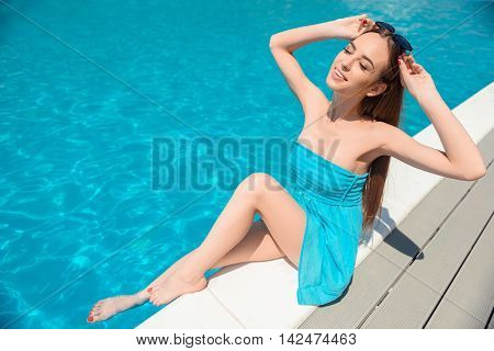 Carefree young girl is bathing her legs in water. She is sitting near swimming pool and smiling. Her eyes are closed with enjoyment