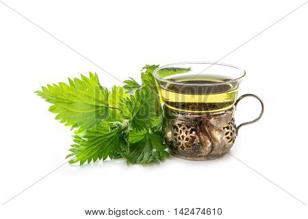 vintage teacup of glass and silver with nettle tea and some fresh leaves isolated with shadows on a white background medicinal plant from nature's pharmacy selected focus narrow depth of field