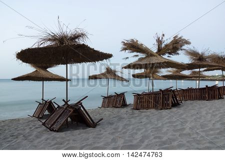 thatched umbrellas and deck chairs stacked at night on the beach waiting for morning visitors